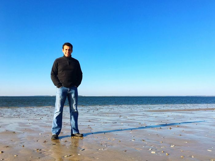 Full length of man standing at beach against clear blue sky