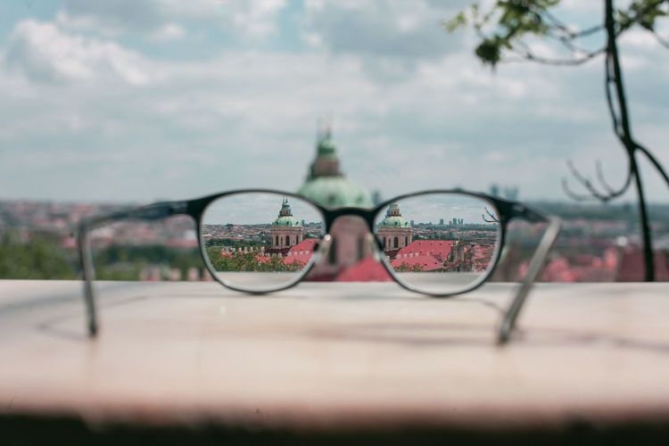 Close-up of eyeglasses on glass against sky