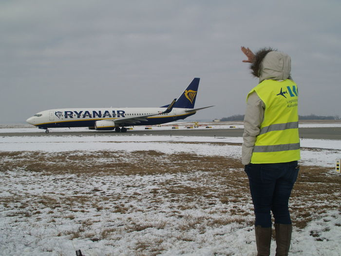 Rear view of man standing on airplane against sky during winter
