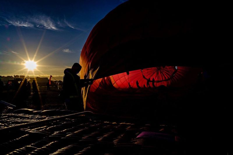 Silhouette man in hot air balloon against sky at sunset