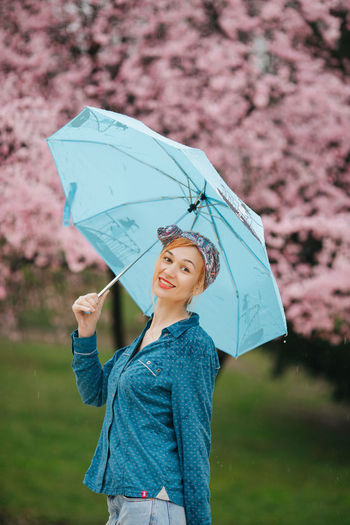 Low section of woman with umbrella standing in rain