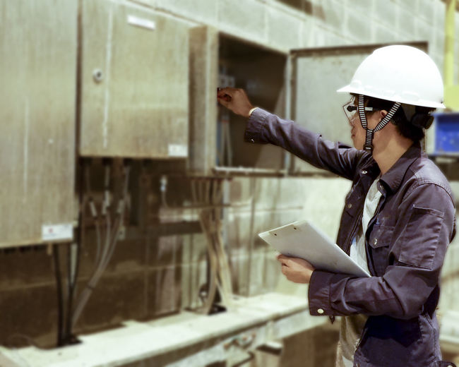 Manual worker wearing hardhat while working in factory