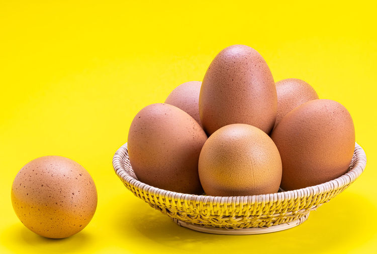 Close-up of eggs on table against yellow background