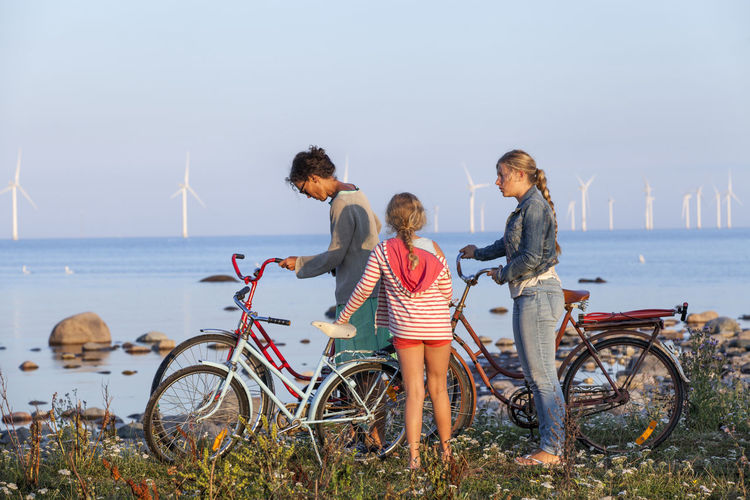 People on bicycle by sea against sky
