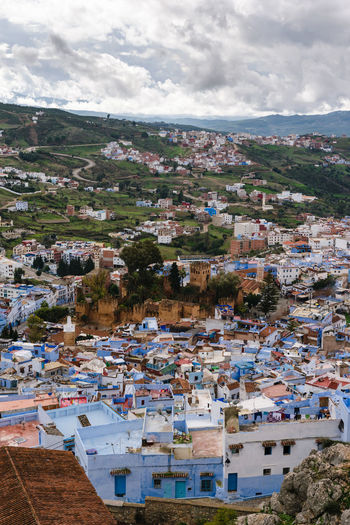 An awesome panoramic view over the blue painted and famous city Chefchaouen in Morocco. It is located in the Rif Mountains. The sky is cloudy. Africa Architecture Background Berber  Blue Chaouen Chefchaouen City Cityscape Culture Medina Morocco Mountain Mountain Range Nature Old Panorama Panoramic Rif Rif Mountains Sky Street Town Travel View
