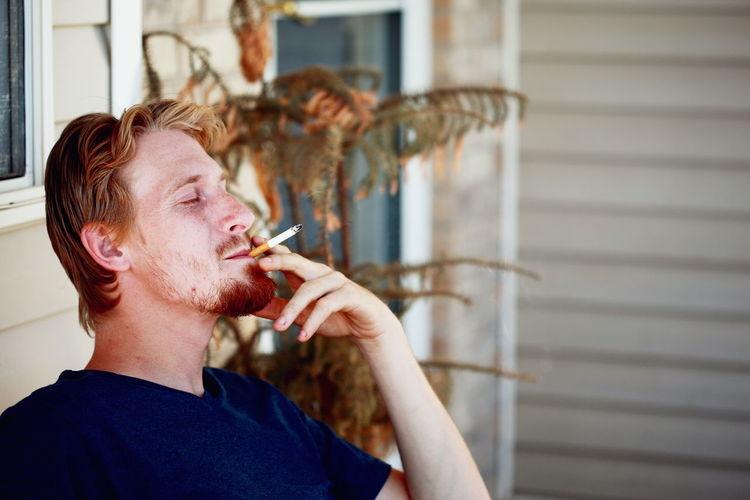 Young Man Smoking Cigarette At Porch