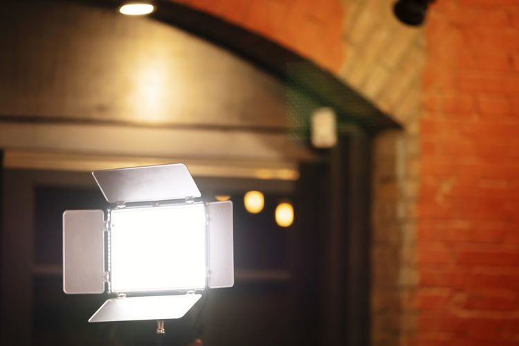 Low angle view of illuminated lamp on wall