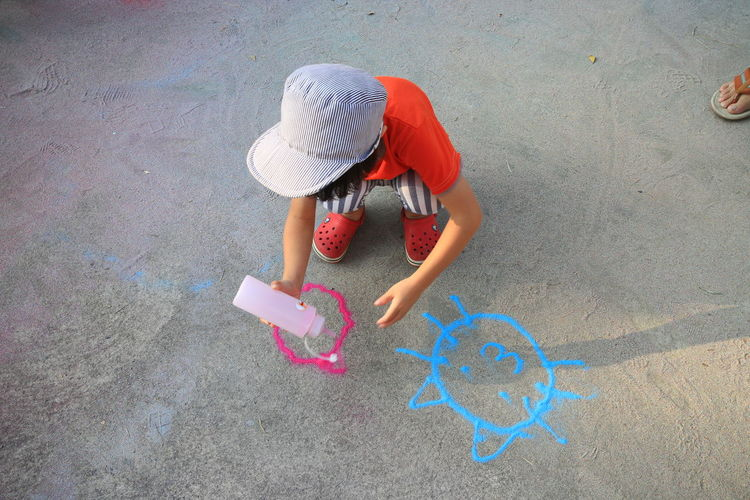 High angle view of boy drawing with powder paint on footpath