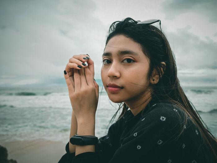 Portrait of woman holding sunglasses against sea