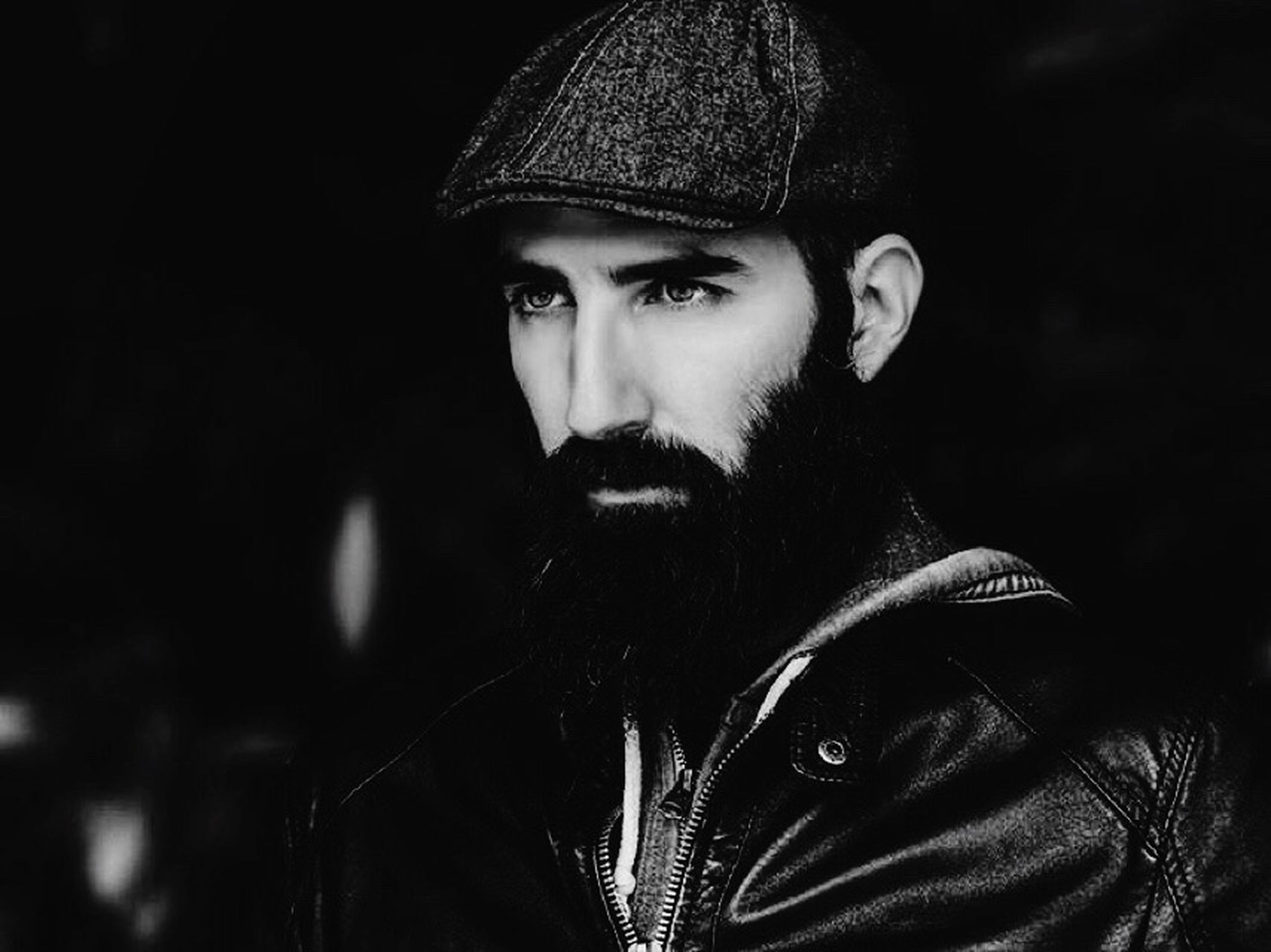 portrait, looking at camera, one person, one man only, only men, individuality, handsome, real people, adults only, headshot, beard, confidence, young adult, adult, night, black background, people, outdoors, warm clothing, close-up