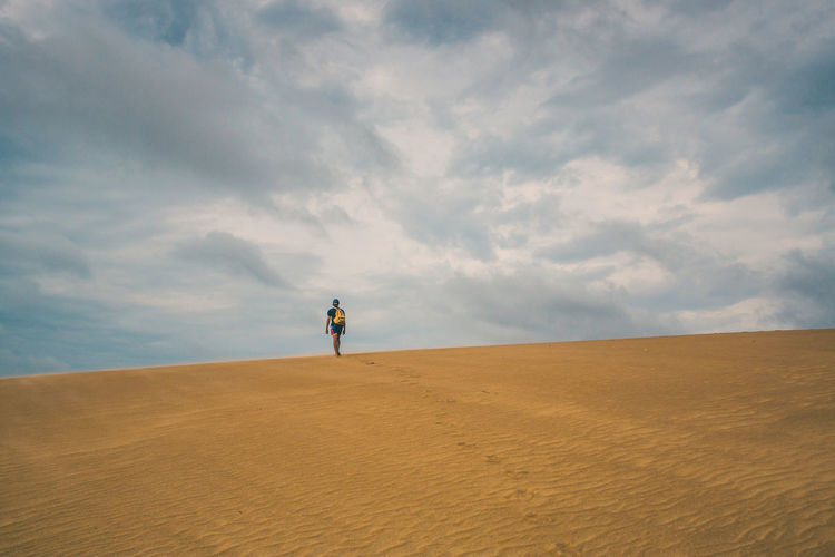 Rear view of man with backpack walking on sand dune in desert