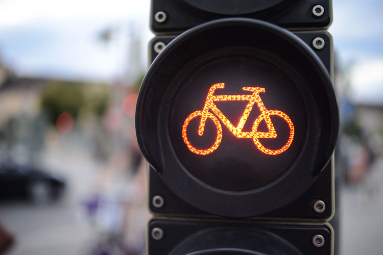 Close-Up Of Bicycle Sign Against Blurred Background