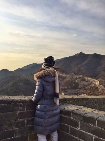 Rear view of woman standing by fortified wall at great wall of china