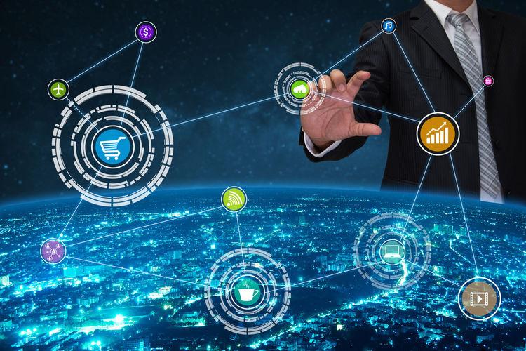 Digital composite image of businessman gesturing towards various icons