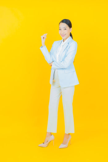 Full length portrait of woman standing against yellow background