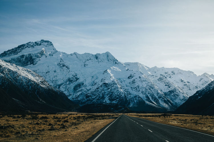 Scenic view of snowcapped mountains against sky with road