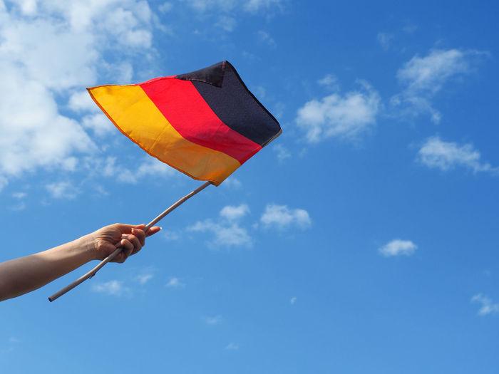 Cropped Hand Waving German Flag Against Sky