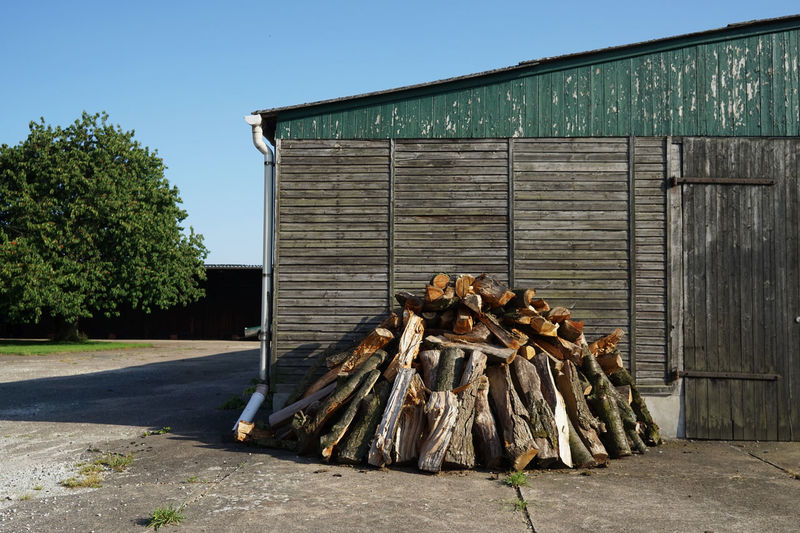 wood stack in front of a barn Architecture Wood - Material Building Exterior Nature Sky Built Structure Tree Day Plant No People Building Clear Sky Log Outdoors Agricultural Building House Barn Wood Timber Firewood Wood Stack