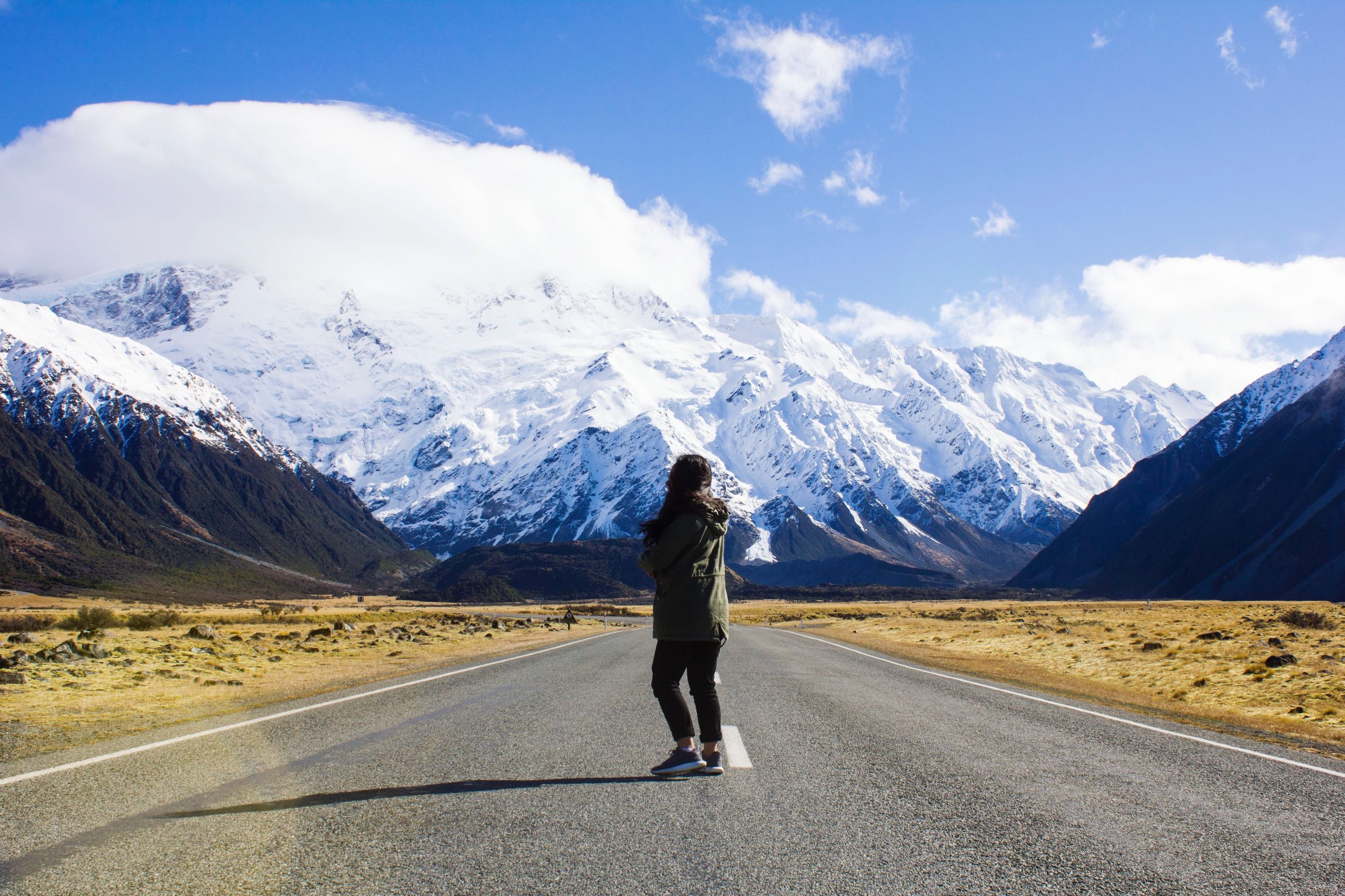 mountain, one person, road, full length, transportation, lifestyles, leisure activity, cloud - sky, sky, beauty in nature, mountain range, real people, scenics - nature, nature, rear view, day, winter, snow, environment, snowcapped mountain