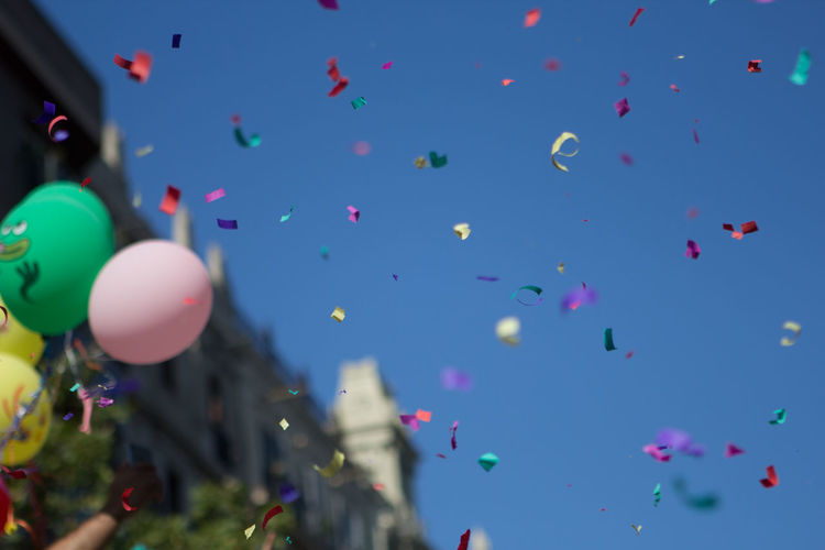 Low Angle View Of Balloons And Confetti Against Clear Blue Sky