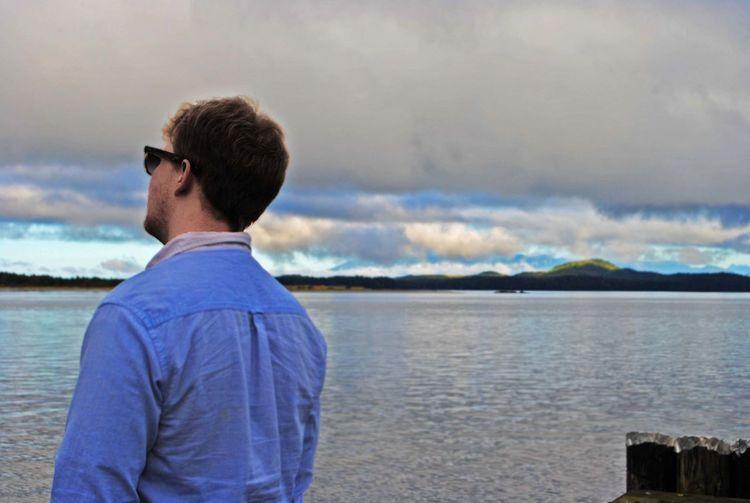 Man wearing sunglasses by lake