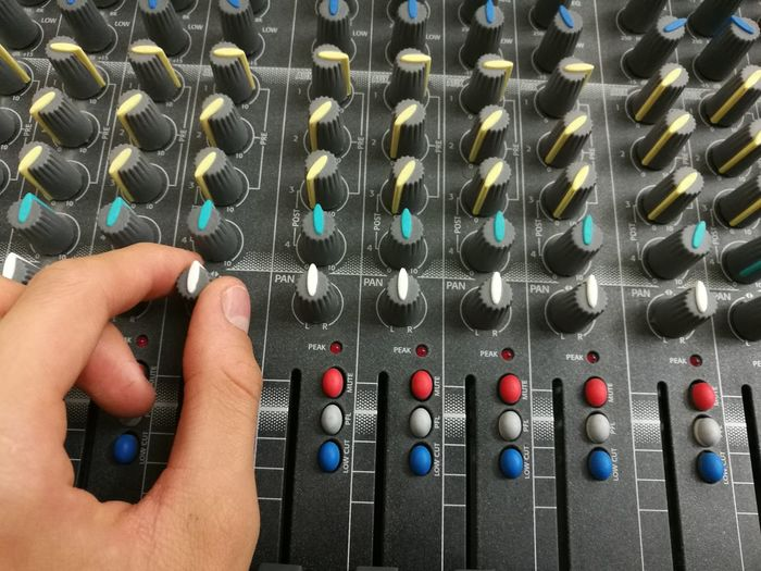 Cropped hands of musician mixing sound with console