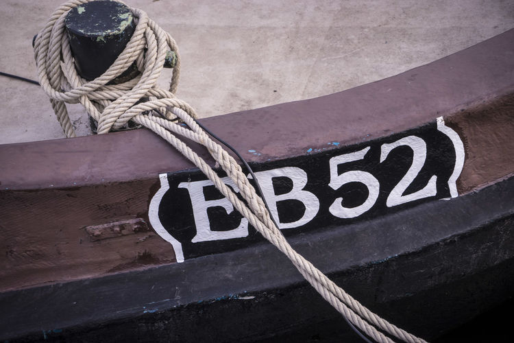 High Angle View Of Rope Tied On Bollard At Harbor
