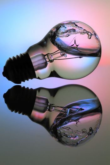 Close-up of electric bulb with water on floor with reflection