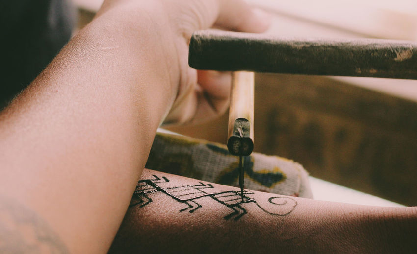 Cropped hand of artist making tattoo