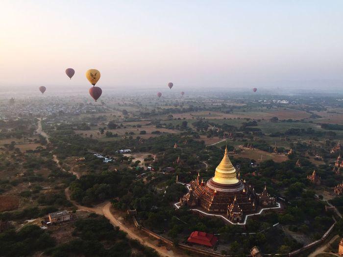 Hot air balloons over pagoda against sky