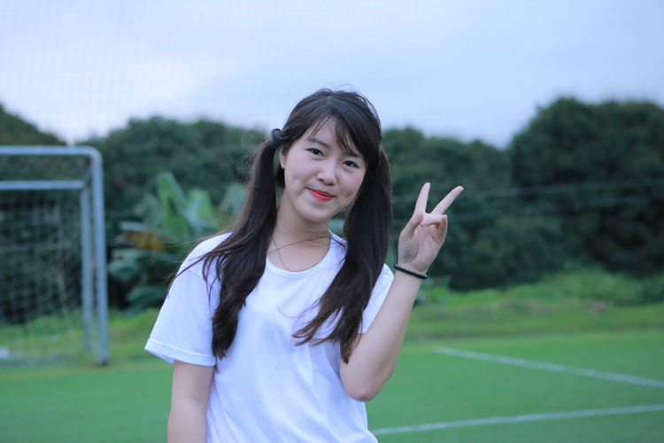 Portrait of smiling young woman gesturing peace sign while standing on playing field