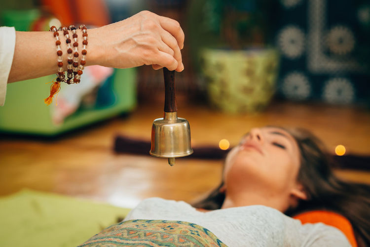 Cropped Hand Of Therapist Holding Bell By Young Woman At Spa