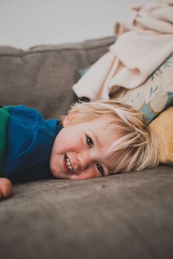 Lying Down Real People One Person Portrait Furniture Lifestyles This Is Family Leisure Activity Relaxation Looking At Camera Home Interior Child Childhood Beach Smiling Resting Headshot Lying On Back Blanket Hair Innocence