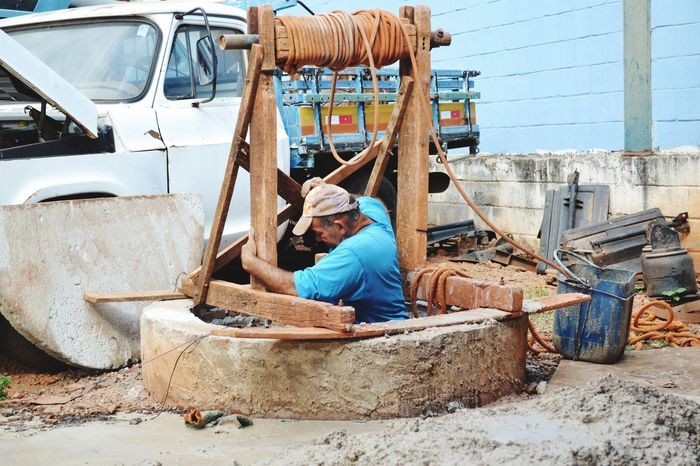 Transportation Mode Of Transport Day Real People One Person Occupation Men Outdoors Nautical Vessel One Man Only Only Men People Mud Working Hard Working Work Water_collection Cistern Wood Wood - Material Tired Old Buildings Old Oldschool