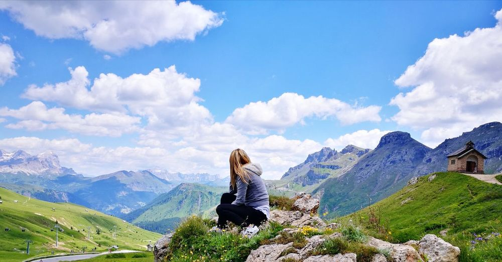 Side view of mature woman sitting on mountain against cloudy sky