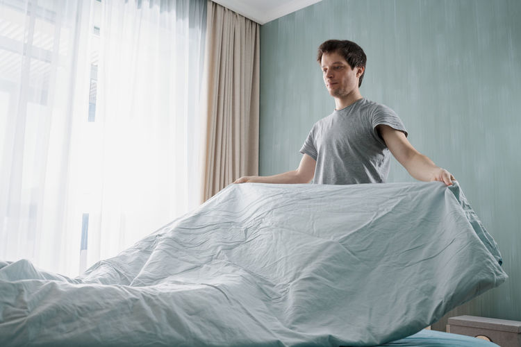 Young man standing on bed