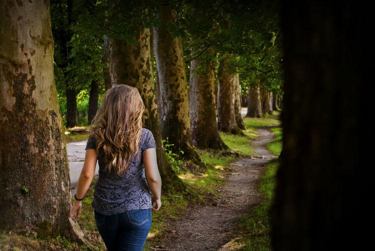 REAR VIEW OF WOMAN WALKING ON FOOTPATH