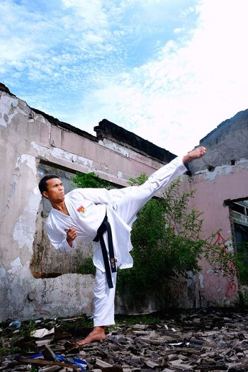 Mid adult man practicing karate at abandoned house