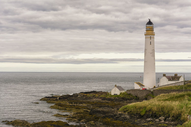 Lighthouse By Sea Against Cloudy Sky At Montrose