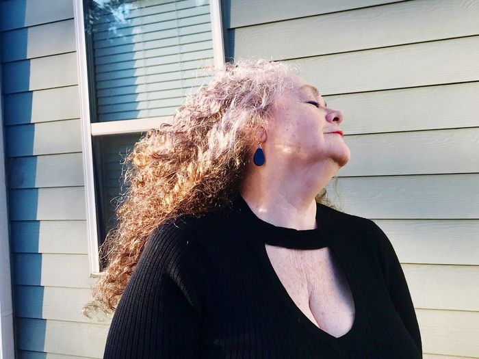 Mature Woman Standing Against Built Structure