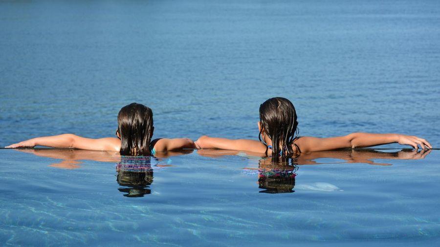 Rear view of girls in infinity pool against sea