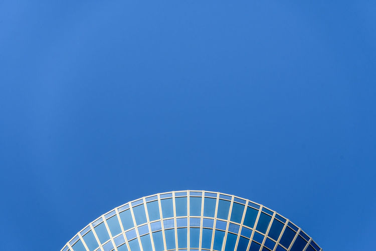 Low angle view of patterned building against clear blue sky during sunny day
