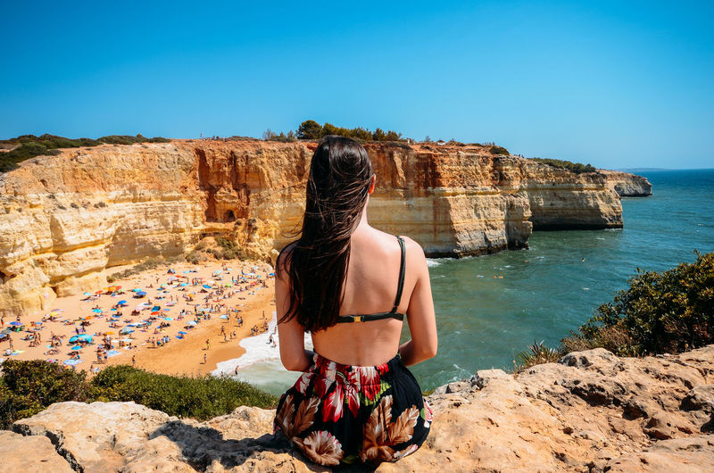 Rear view of woman looking at sea against clear sky