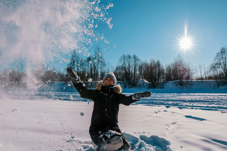 Man with arms outstretched in snow during winter