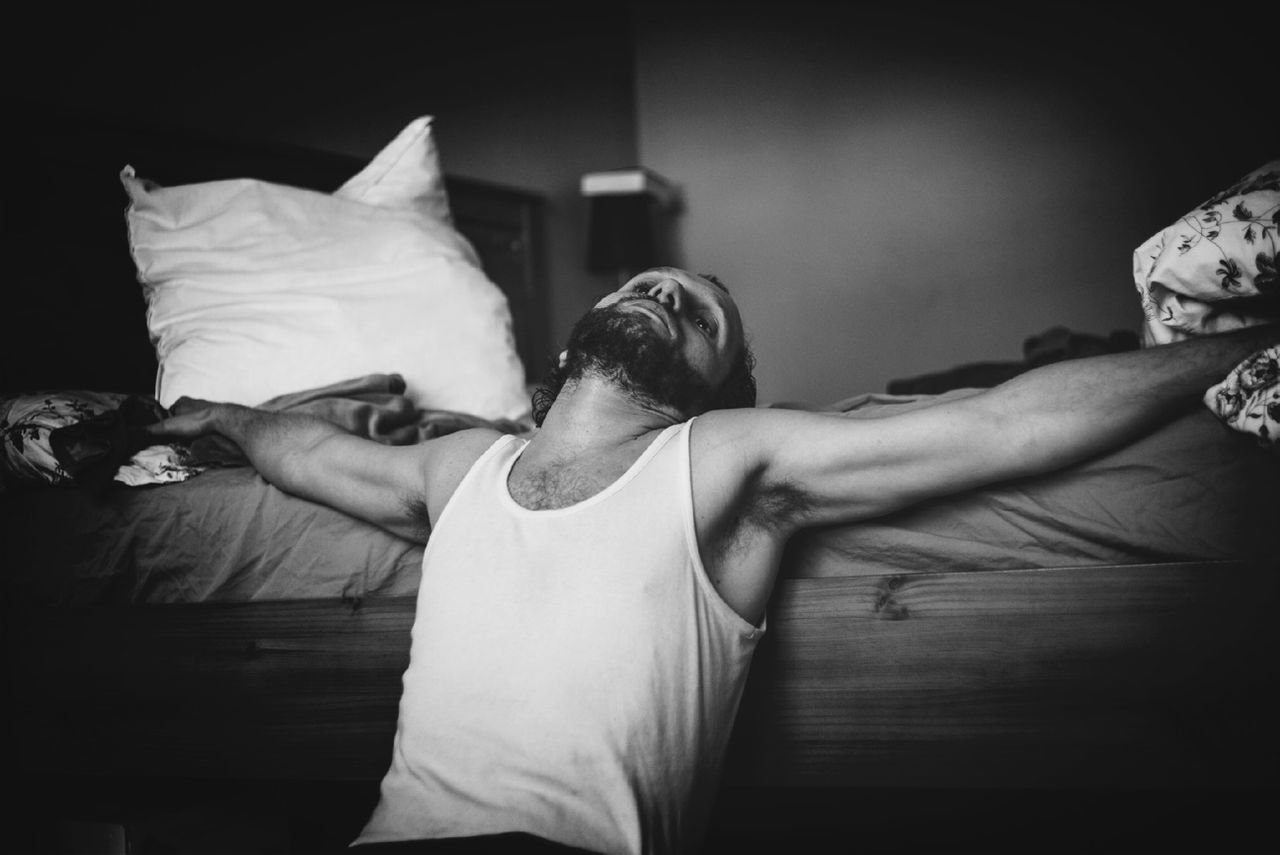Man relaxing with arms outstretched by bed at home