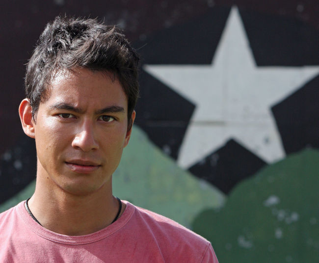 Young eurasian adult looking into the camera with a serious look in front of a wall with a star.