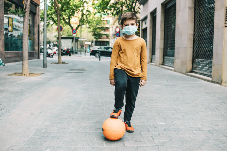 Little boy playing football with a mask