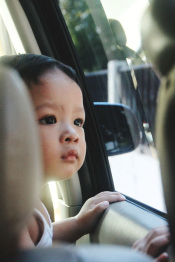 Close-up of cute baby boy looking through window in car