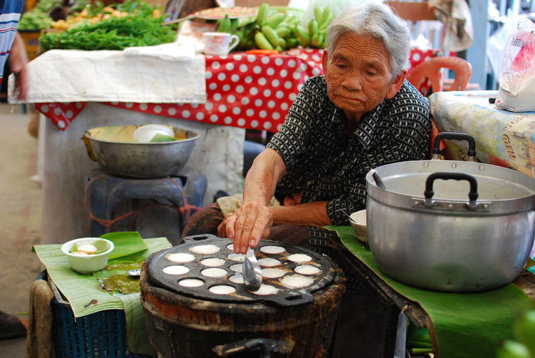 Senior woman preparing food at street market
