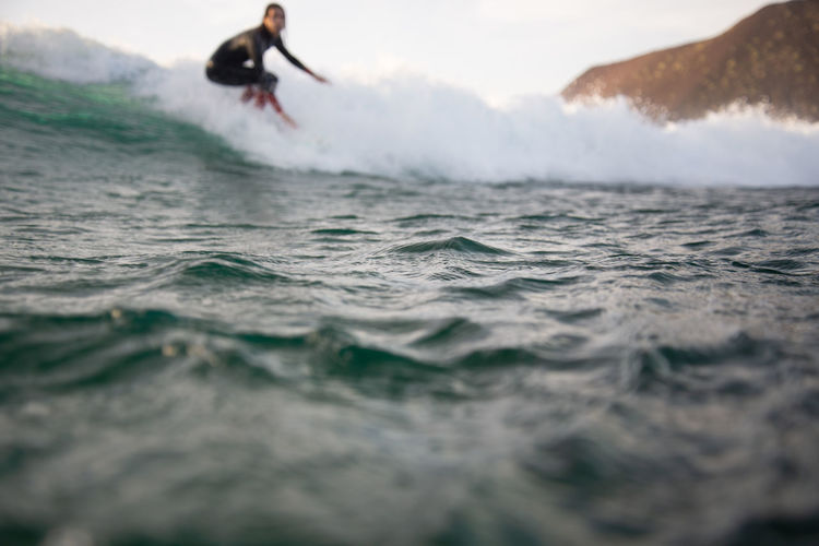 Sea Sport Water Motion Wave Leisure Activity Surfing Aquatic Sport One Person Lifestyles Waterfront Selective Focus Real People Skill  Extreme Sports Adventure Beauty In Nature Day Outdoors